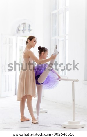 The little ballerina in tutu with personal classic ballet teacher in dance studio posing at ballet barre on a white studio background - stock photo