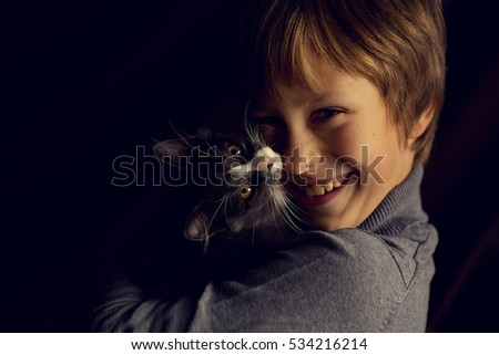 The little blonde boy hugging a gray kitten. Beautiful portrait. Children and animals.
