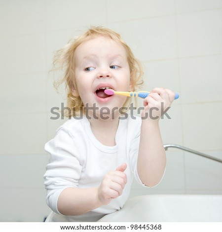 The little blonde girl brushing her teeth with a toothbrush in the bathroom. Hygiene. The girl wearing a blank white shirt. Ready for your design or logo