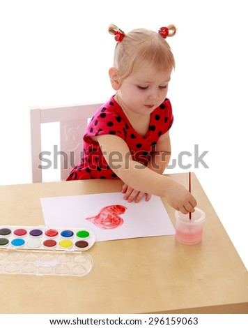 The little blonde girl in a red summer dress polka dot lowers the brush with water, girl paints with watercolors sitting at the table - isolated on white background
