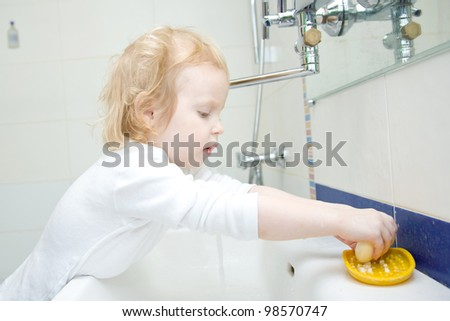 The little blonde smiling girl washing hands and face with soap in the bathroom. Hygiene. The girl wearing a blank white shirt. Ready for your design or logo