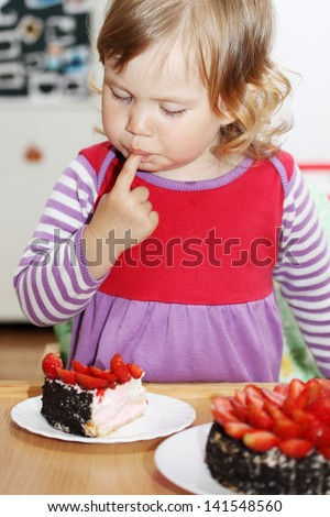 The little blue-eyed girl eating cake with strawberries - stock photo