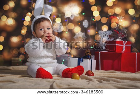 The little boy (baby) in the New Year's bunny suit on the background of the Christmas garland and gift boxes with ribbon. - stock photo