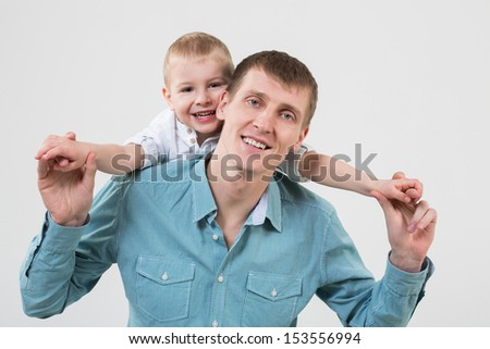 The little boy behind his father hugs him in studio - stock photo