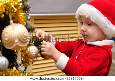 the little boy decorates a Christmas tree on the Christmas eve - stock photo