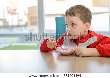 The little boy eating fruit yoghurt in a bowl. Dressed in a red sweatshirt sitting at a table at home - stock photo