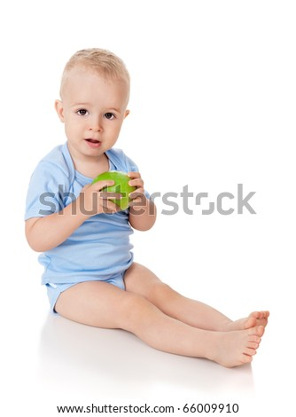 The little boy eats a green apple