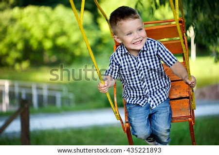 The little boy having fun on the orange swing on a green background.