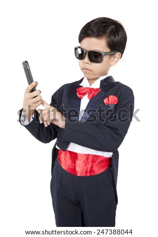 The little boy in a business suit speaks by phone - stock photo