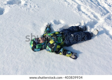 The little boy in a color jacket with a hood with a smile lying on snow