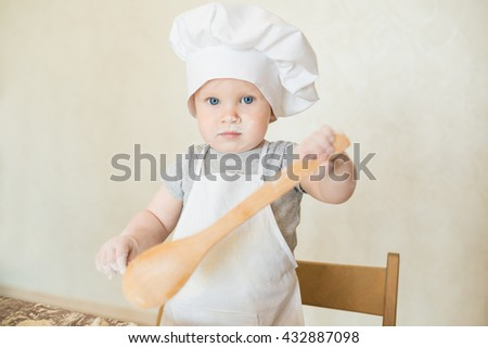 The little boy in a suit of the cook sculpts dough. Baby make dinner in chef suit - stock photo