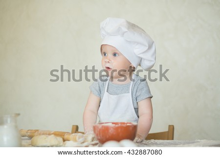 The little boy in a suit of the cook sculpts dough. Baby make dinner in chef suit. Kid wonders, surprised something - stock photo