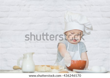 The little boy in a suit of the cook sculpts dough. Baby scullion make dinner in chef suit. Cooking concept with free text space - copy space - stock photo