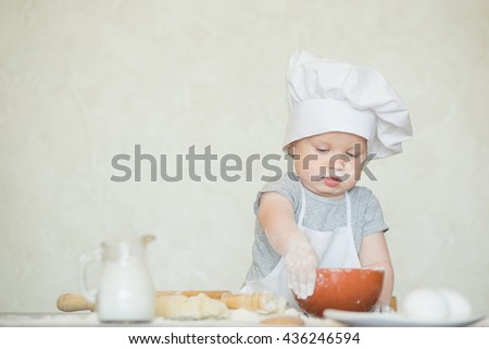 The little boy in a suit of the cook sculpts dough. Baby scullion make dinner in chef suit. Cooking concept