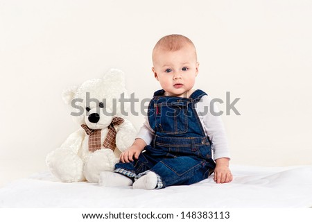 the little boy in blue overalls plays with a teddy bear on a light background