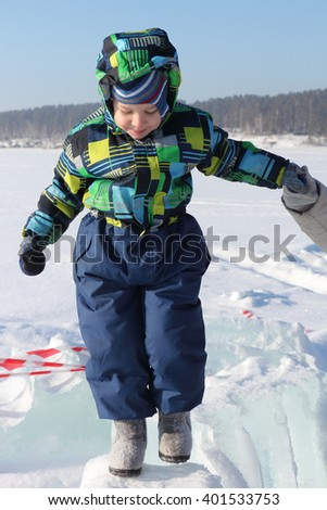 The little boy in color overalls going on ice holding the adult's hand