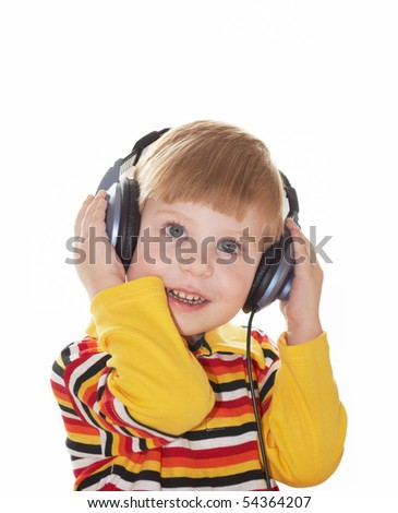 The little boy in headphones listens to music on a white background