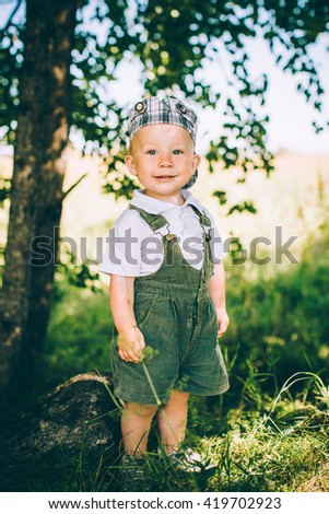 The little boy in overalls and a cap on the nature