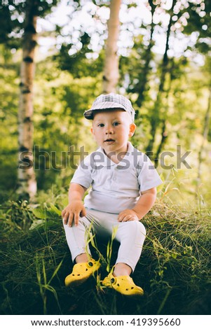 The little boy in shorts and a cap near a tree