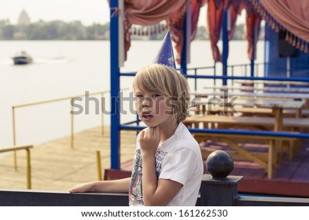 The little boy in the clown cap stands alone in a landscape. - stock photo