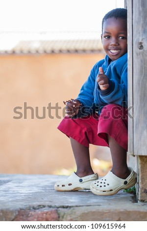 The little boy is sitting on the stairs. - stock photo