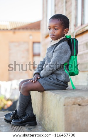 The little boy is waiting for the bus to pick him up for school. - stock photo
