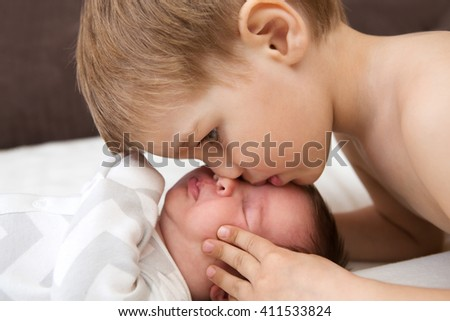 the little boy kisses the newborn sister