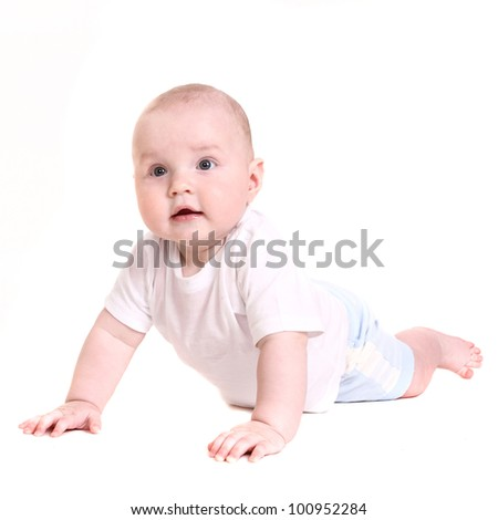 the little boy lies on a stomach. it is isolated on a white background.