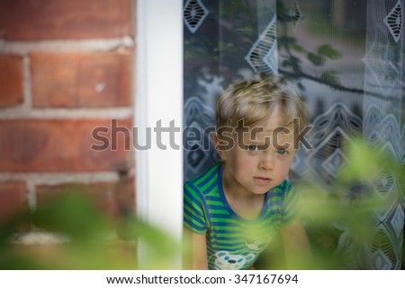 The little boy looks out of the window. - stock photo
