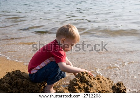 The little boy plays sand at the sea.