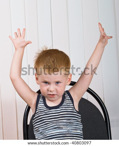 The little boy sits on a chair