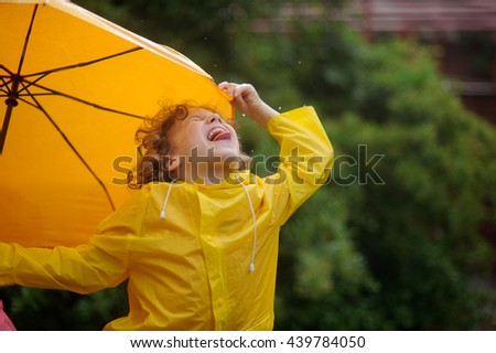The little boy tongue catches rain drops. He has thrown back the head and has closed eyes. A hand holds an umbrella. - stock photo