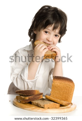 The little boy which eating a  bread on desk - stock photo