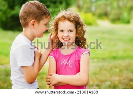 The little boy whispers a secret on an ear to the girl. - stock photo