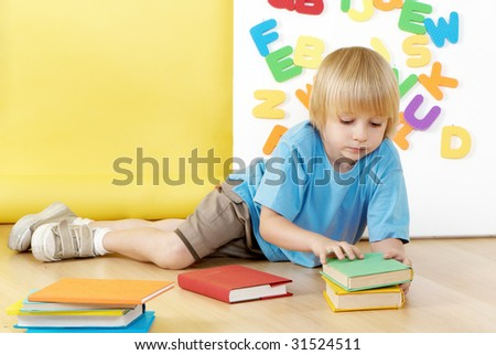 The little boy with books in a kindergarten.
