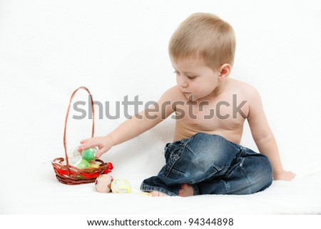 The little boy with Easter eggs on a white background