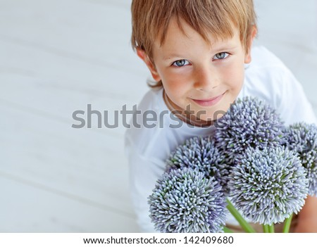 The little boy with flowers - stock photo