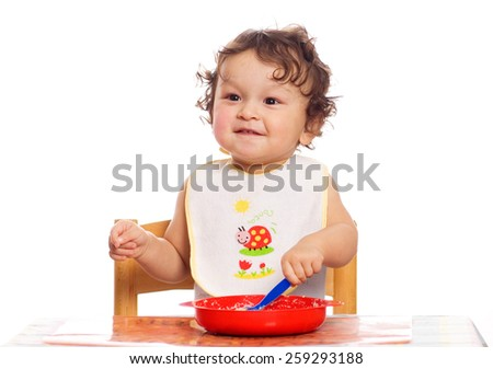 The little child studies to eat independently. - stock photo