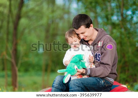 The little daughter on his father's lap. Family walk