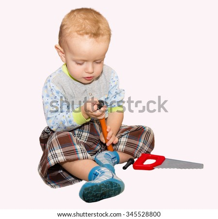 The little fair-haired boy plays with plastic toys: a hammer and a saw. The isolated picture on a white background