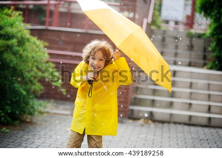 The little fellow in yellow raincoat is in the yard under a pouring rain.Two hands he holds an open yellow umbrella. Large drops of a rain.To the boy it is cheerful.He with a smile looks in the camera - stock photo