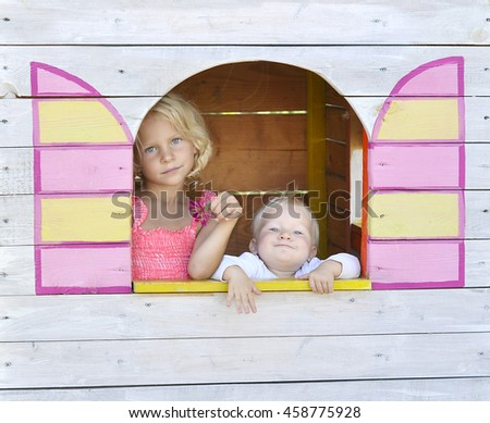 The little girl and the baby look out the window of a small toy house. - stock photo