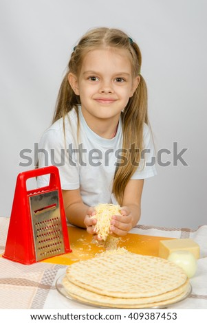 The little girl at the table rubbed grated cheese for pizza