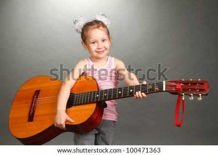 the little girl costs with a big guitar in hands, a look in a lens, smiles, a double 5
