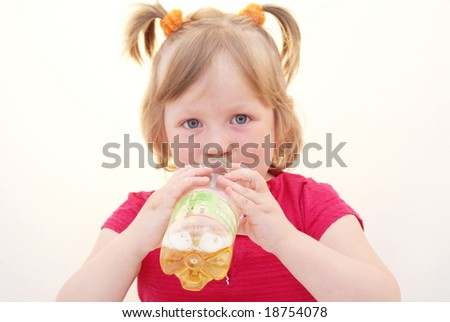 The little girl drinking from bottles of apple juice. Isolated on a white background.