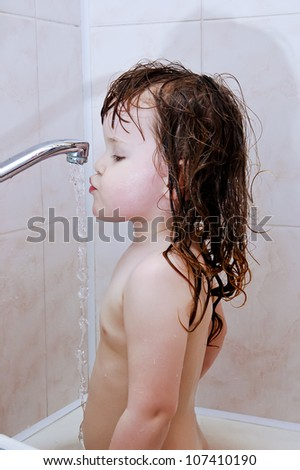 the little girl drinks water from the crane during bathing - stock photo