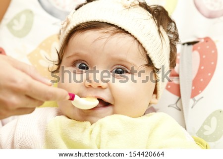 The little girl eating marrow puree from a spoon, sitting in a chair for feeding