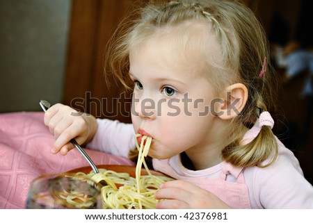 The little girl eats tasty macaroni