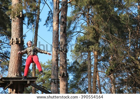 The little girl goes down on the bungee in the forest - stock photo