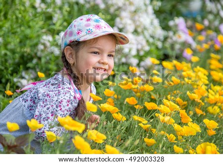 the little girl happily laughing in the flowers